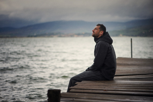 Lonely man sitting on pier under rain